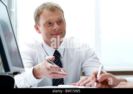 Portrait of businessman explaining work to his colleague - Stock Photo