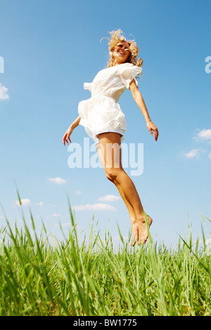 Photo of happy girl leaping over green grass on summer day - Stock Photo