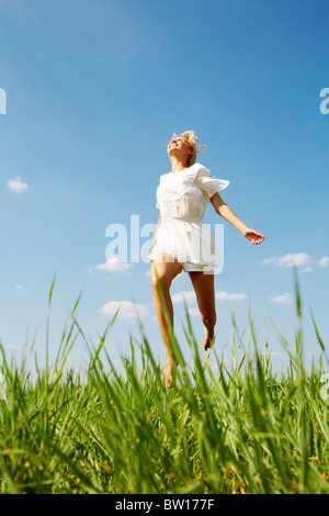 Photo of happy girl running down green grass on sunny day - Stock Photo