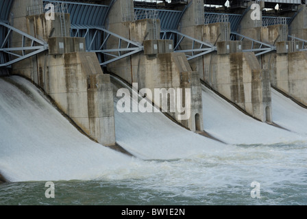 Close up showing the gates on a dam with water flowing through them - Stock Photo