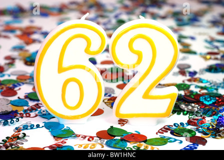 Number 62 celebration candle with confetti. - Stock Photo