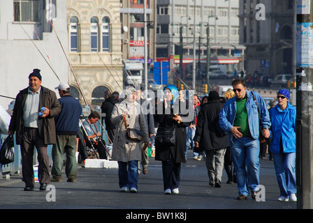 ISTANBUL, TURKEY. Pedestrians crossing the Galata Bridge over the Golden Horn, with Karakoy district in the background. - Stock Photo