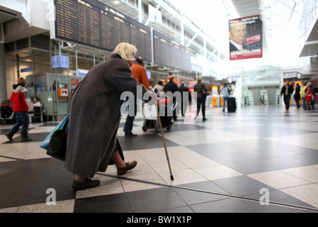 An old woman walking through the terminal of the Franz Josef Strauss Airport, Munich, Germany - Stock Photo
