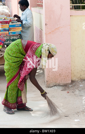 Indian woman sweeping the streets in Puttaparthi, Andhra Pradesh, India - Stock Photo