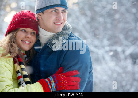 Portrait of happy young family spending time outdoors in winter - Stock Photo