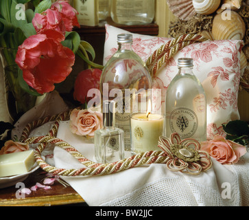 Still-Life of lighted candle in holder with glass bottles and pink+white cushion and red tulips - Stock Photo
