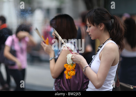 Local woman pay their repects at the Erawan Shrine, a highly religious site in central Bangkok, Thailand. - Stock Photo