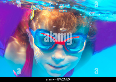 Underwater swimming girl goggles blue water portrait - Stock Photo
