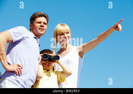 Portrait of family members looking afar where female showing - Stock Photo