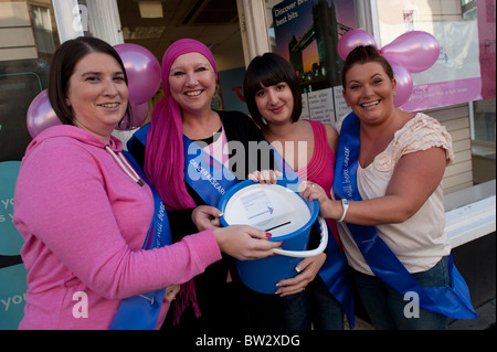 four women shop workers volunteers dressed in pink collecting money for cancer research, UK - Stock Photo