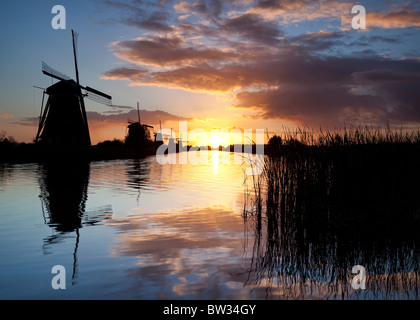 A row of windmills at sunrise at the famous Kinderdijk landmark, Netherlands - Stock Photo