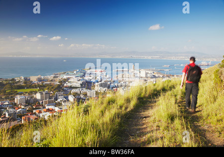 Man hiking on Signal Hill with Victoria and Alfred Waterfront in background, Cape Town, Western Cape, South Africa - Stock Photo