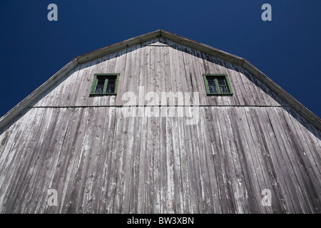 Partial view of the side of an old Mansard style wooden barn, Laval, Quebec, Canada - Stock Photo