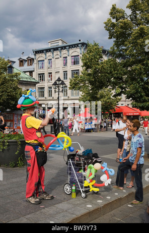 Street performer entertaining tourists at Place Jacques Cartier in Old Montreal in summertime, Quebec, Canada - Stock Photo