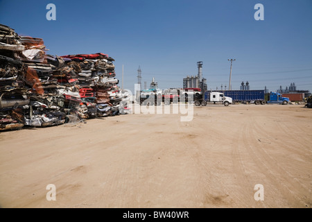 Stacked and crushed cars and trucks arriving at a scrap metal recycling yard, Quebec, Canada - Stock Photo