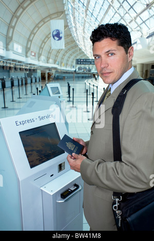 Businessman using express check in at airport, Toronto, Canada - Stock Photo