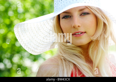 Portrait of pretty young lady in elegant hat looking at camera - Stock Photo