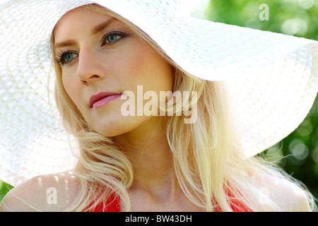 Pretty young lady in elegant hat looking aside at summer - Stock Photo