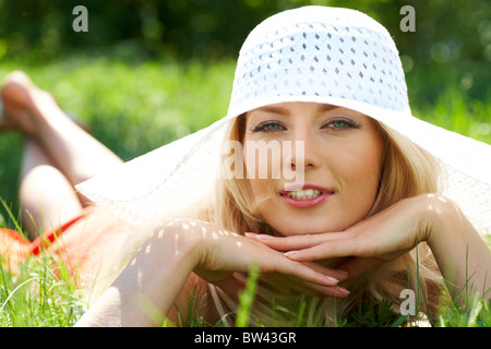 Pretty young lady in elegant hat relaxing in green grass - Stock Photo