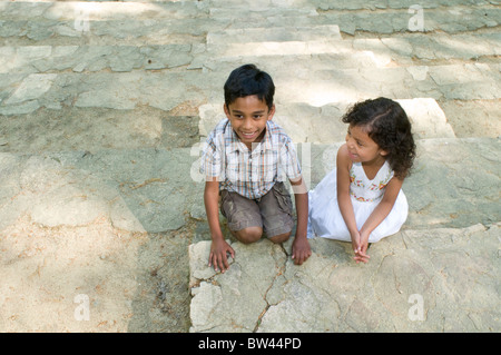 Two siblings on historic, stone steps at the Forest Theater in Chapel Hill, North Carolina, USA - Stock Photo