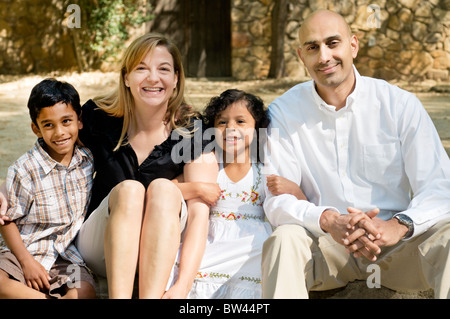 A mixed race family portrait of a 5-year-old Indian boy, a Guatemalan man, a Caucasian woman, and a 4-year-old Guatemalan - Stock Photo