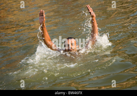 An Indian man swimming in the Ganges, Varanasi, India - Stock Photo