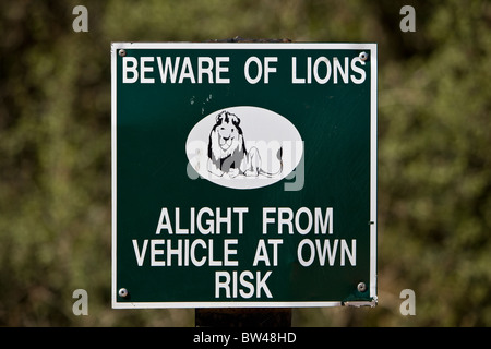 A sign warns visitors to Addo Elephant Park in South Africa that there is danger from lions within the park's confines. - Stock Photo