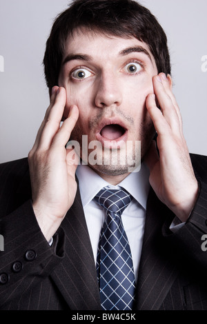 Funny portrait of amazed young business man