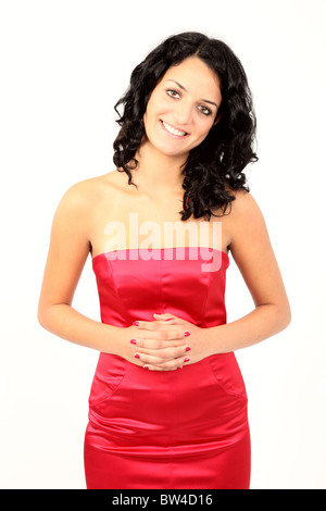 Pretty Asian girl wearing a red dress hands together smiling at camera - Stock Photo