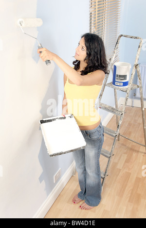 Young woman using a roller with white paint to walls - Stock Photo