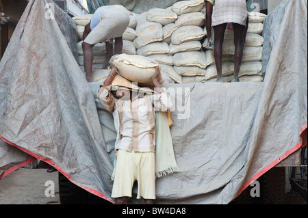 Indian men offloading bags of cement from a lorry to construction building site. Andhra Pradesh, India - Stock Photo