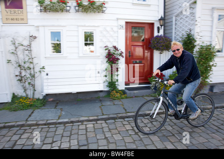 A local man cycling past traditional white wooden houses in the old 'Gamle' Stavanger district, Stavanger, Rogaland, - Stock Photo