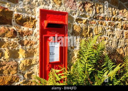 Rural red royal mail  post box on wall - Stock Photo