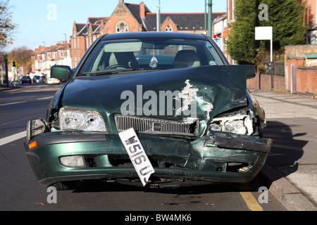 An accident damaged car on a U.K. street. - Stock Photo