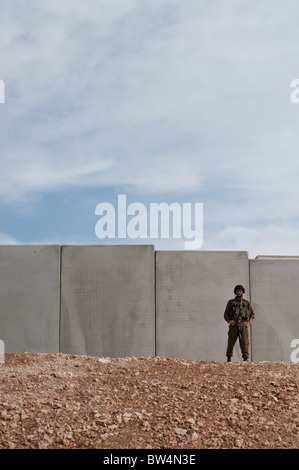 An Israeli soldier stand in front of the Israeli separation barrier which threatens to encircle the West Bank town - Stock Photo