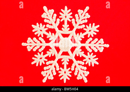 single white snowflake isolated over red - Stock Photo
