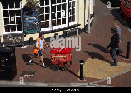 Postman pushing his mail trolley past Poole High Street, Dorset in August Summer - Stock Photo