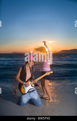 Cple play guitar and dance at sunset sea - Stock Photo
