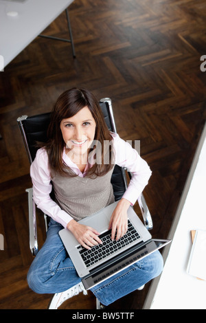 Woman typing on laptop looking to camera - Stock Photo