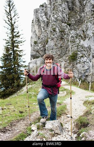Man with hiking poles on mountain trail - Stock Photo