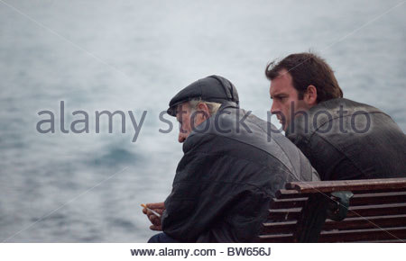 Old person thinking and talking to a younger man - Stock Photo