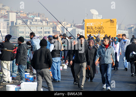 ISTANBUL, TURKEY. People walking over, and fishing from, the Galata Bridge, with Karakoy district in the background. - Stock Photo