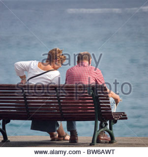 Couple sitting on a wooden bench - Stock Photo