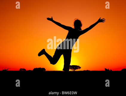 Silhouette of a young woman jumping at the sunset - Stock Photo