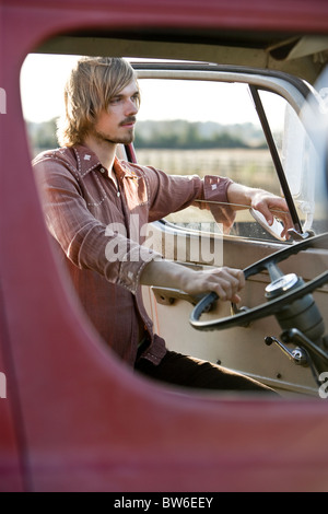 Young man climbing in van, 1970s style - Stock Photo
