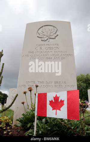 View of the Canadian flag on a grave in the Beny-Sur-Mer Canadian Commonwealth War Cemetery, Normandy, France. - Stock Photo