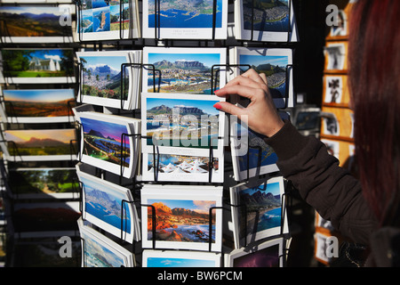 Woman looking at postcards at Victoria and Albert Waterfront, Cape Town, Western Cape, South Africa - Stock Photo