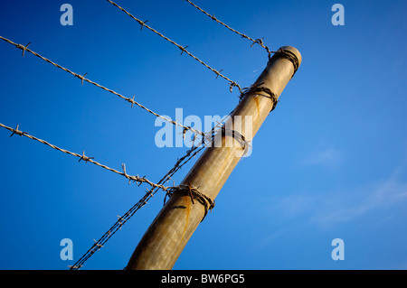 Fence posts with barbed wire running across it against a blue sky - Stock Photo