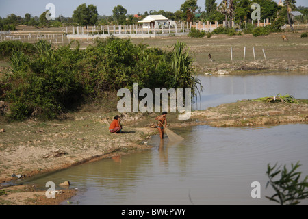 Local woman fishing by net in shallow waters off the beach for Local fishing ponds