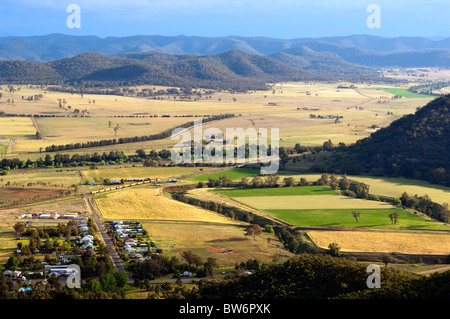 Beautiful country area with small town and brightly colored fields - Stock Photo